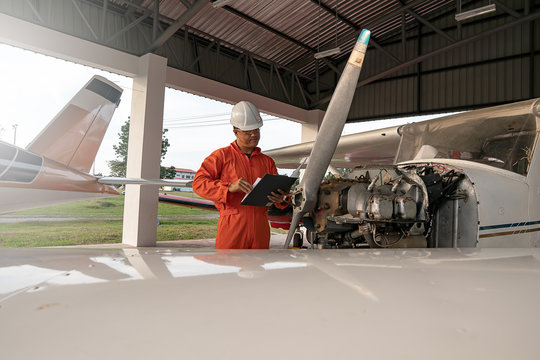 Asian male engineers were checking the availability of aircraft