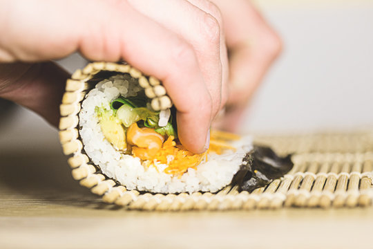 Process of rolling up sushi roll with salmon using bamboo mat, viewed from the side in closeup