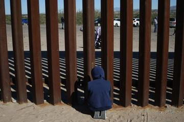 personas se saludan entre el muro que divide mexico de estados unidos
