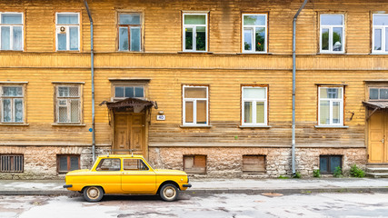 Tallinn in Estonia, wooden yellow house, typical facade in Kalamaja, with a yellow car in the street