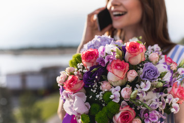 Happy smiling girl speaking on handy at blurred background. Focus on bouquet being hold by her. Copy space on left side
