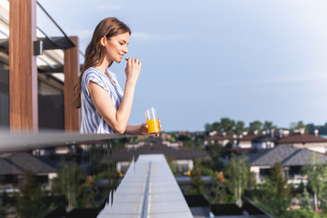 Profile of cheerful lady is holding glass of orange juice and looking ahead with smile. Copy space on right side