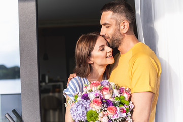 Happiness in air. Happy smiling couple is hugging . Man kissing female forehead. Copy space on left side