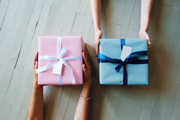 Top view of women hands holding gift boxes. Pink and blue present boxes on the wooden background.