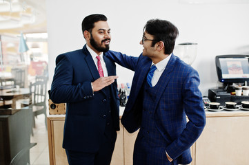 Two indian businessman in suits standing on cafe and discuss each other.