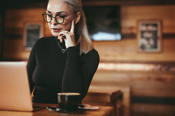 Mature business woman at cafe using laptop