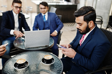 Group of indian business man in suits sitting at office on cafe with laptop, texting on phones and making photo of coffee.