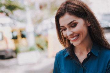 Concept of success and well-being. Close up portrait of smiling beautiful lady in stylish cloth being on street. Copy space on left