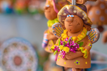 Christmas and New Year holiday background. Funny angel with flowers. Clay toys on the market.