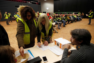 Protesters wearing a yellow vests, the symbol of a French drivers' protest against higher diesel fuel prices, vote to elect a representative to liaise with other blockade points