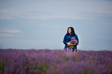 Young girl in blue dress, posing in a lavender field.