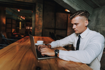 Concept of success and well-being. Waist up side on portrait of handsome young businessman working on portable computer in cozy cafe