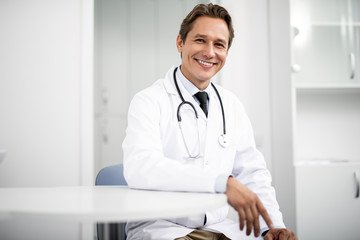 Emotional confident practitioner in white coat smiling and putting one hand on the table while sitting and looking