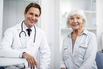 Positive young doctor looking glad while sitting next to the emotional elderly lady and smiling