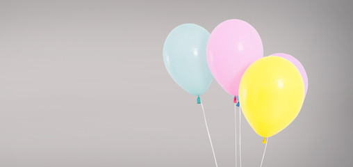 colored helium balloons isolated on grey background, birthday concept