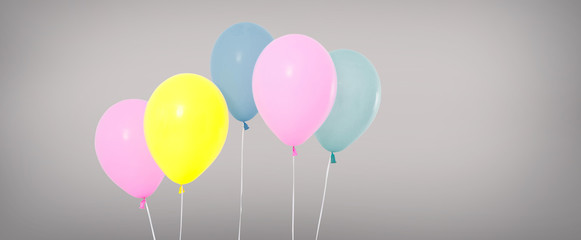 pink,yellow,blue balloons isolated on grey background, birthday holiday