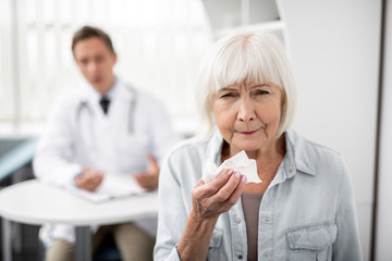Calm elderly woman standing with general practitioner on the background and holding napkin while sneezing