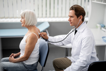 Calm aged woman sitting on the chair and professional general practitioner using stethoscope during the examination