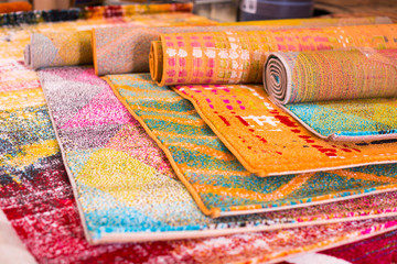 Various colorful wool rugs for sale at store