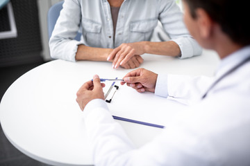 Professional practitioner holding blue pen while sitting at the table in front of his patient