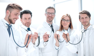 group of doctors hold their stethoscopes