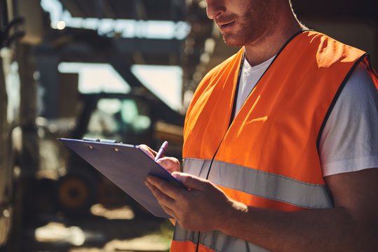 Close up of professional builder in orange uniform standing outdoors and carefully making notes while holding clipboard