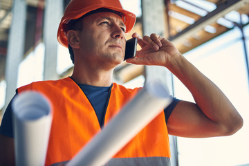 Calm professional builder in orange helmet and vest putting his head up and frowning while talking on the phone