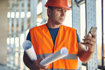 Thoughtful professional builder in orange uniform looking attentively at the screen of his modern device while standing with drawings