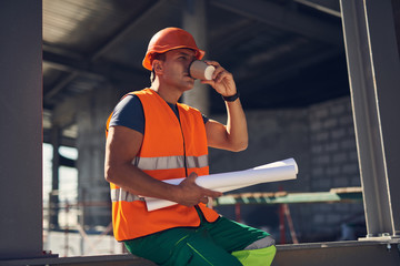Professional calm foreman in orange uniform looking into the distance while holding drawings and drinking coffee from the carton cup