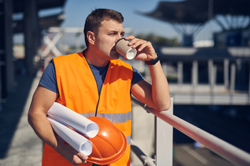 Coffee at work. Young professional builder standing outdoors in sunny day and holding his orange helmet while drinking coffee