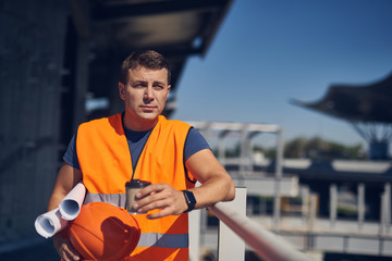 Thoughtful young worker wearing safety vest and holding graphics while standing with a cup of coffee and looking into the distance