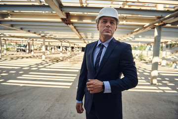 Waist up photo of adult businessman in helmet is standing on construction site. Copy space on left side