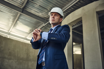 Waist up portrait of adult architect in helmet is checking his smartwatch while standing in facility. Copy space on left side