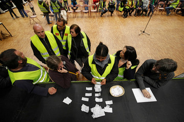 Protesters wearing yellow vests, the symbol of a French drivers' protest against higher diesel fuel prices, count ballots as they elect a representative to liaise with other blockade points in Aubevoye