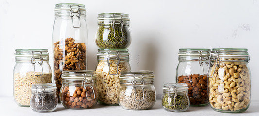 Glass jars with Superfoods nuts and cereals stacked on top of each other