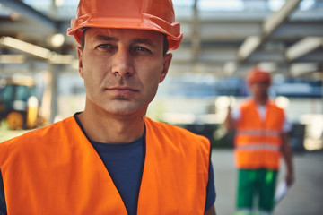 Close up of male employee of construction company is locating in hangar with his colleague on background