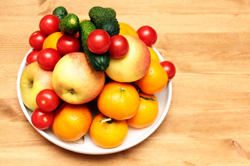 tomatoes, cucumbers, tangerines and apples on a wooden table on a plate