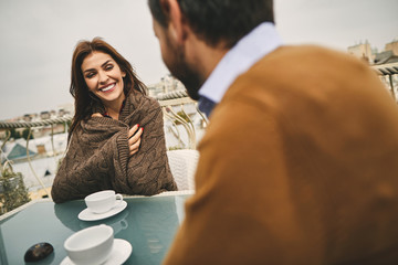 Waist up photo of smiling lady in woolen plaid is sitting in cozy cafe with her boyfriend