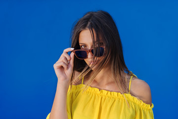 Cute girl in yellow shirt posing in front of blue wall.