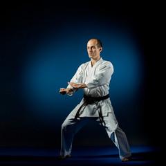 On a blue tatami adult athlete doing formal karate exercises
