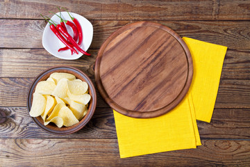 hot red pepper on plate,pizza desk,yellow napkin and potato chips on table, copy space,top view