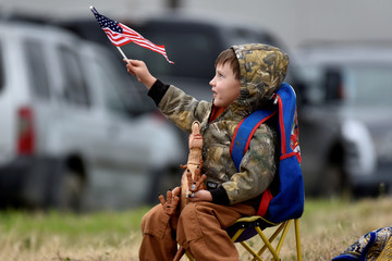 Young spectator waves American flag along route where Bush casket will travel aboard Union Pacific funeral train in Navasota