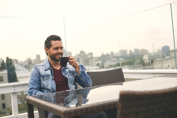 Attractive male with beard is spending time on terrace. Copy space on right side