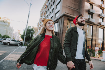 Waist up portrait of cheerful bearded man holding hand of his charming girlfriend. They looking away and smiling