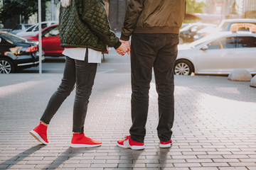 Cropped portrait of lady in jeans sharing tender moment with her boyfriend. They standing on sidewalk while spending time outdoors
