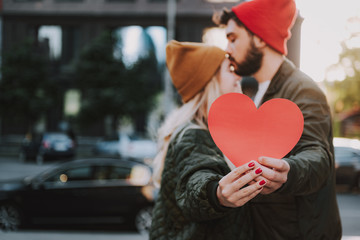Close up of male and female hands holding sign of love. Bearded man in hat kissing forehead of his charming girlfriend