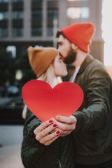 Red paper heart with young couple on blurred background