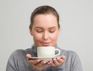 Junge hübsche Frau im grauen Pulli riecht an einer guten Tasse Kaffee
