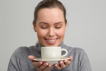 Hübsche Frau hält lächelnd  eine Kaffeetasse in der Hand