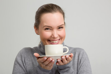 Junge hübsche Frau im grauen Pulli hält lächelnd  eine Kaffeetasse in der Hand